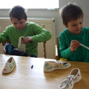 Kluci si malují boty.
